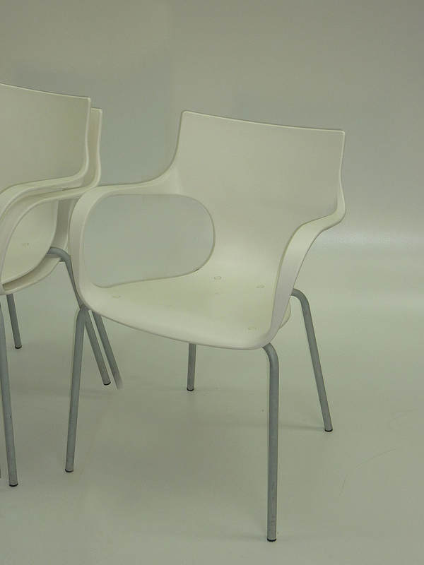 White plastic stacking chairs with arms